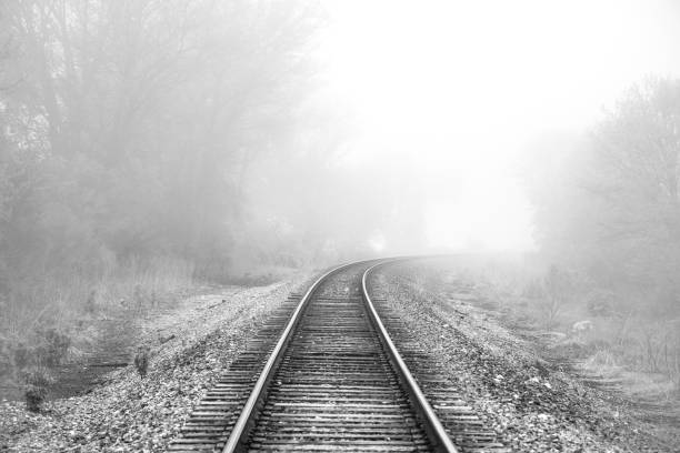 Classic black and white train tracks going off into foggy oblivion. stock photo