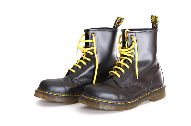 classic black doc martens lace-up boots with yellow laces - postal worker stok fotoğraflar ve resimler