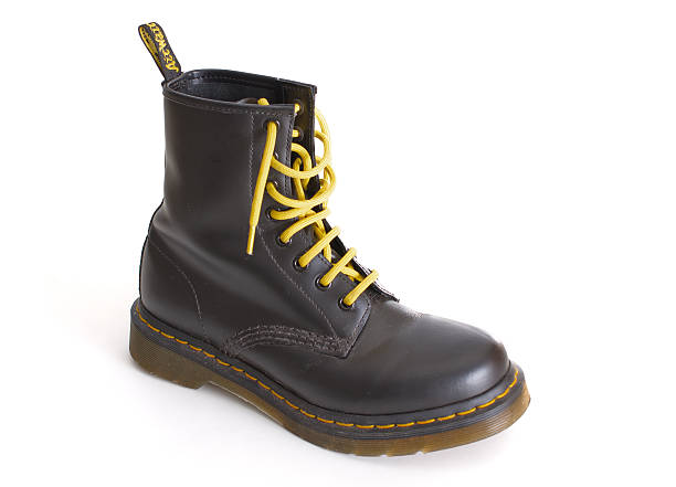 classic black dr. martens lace-up boot with yellow laces - postal worker stok fotoğraflar ve resimler