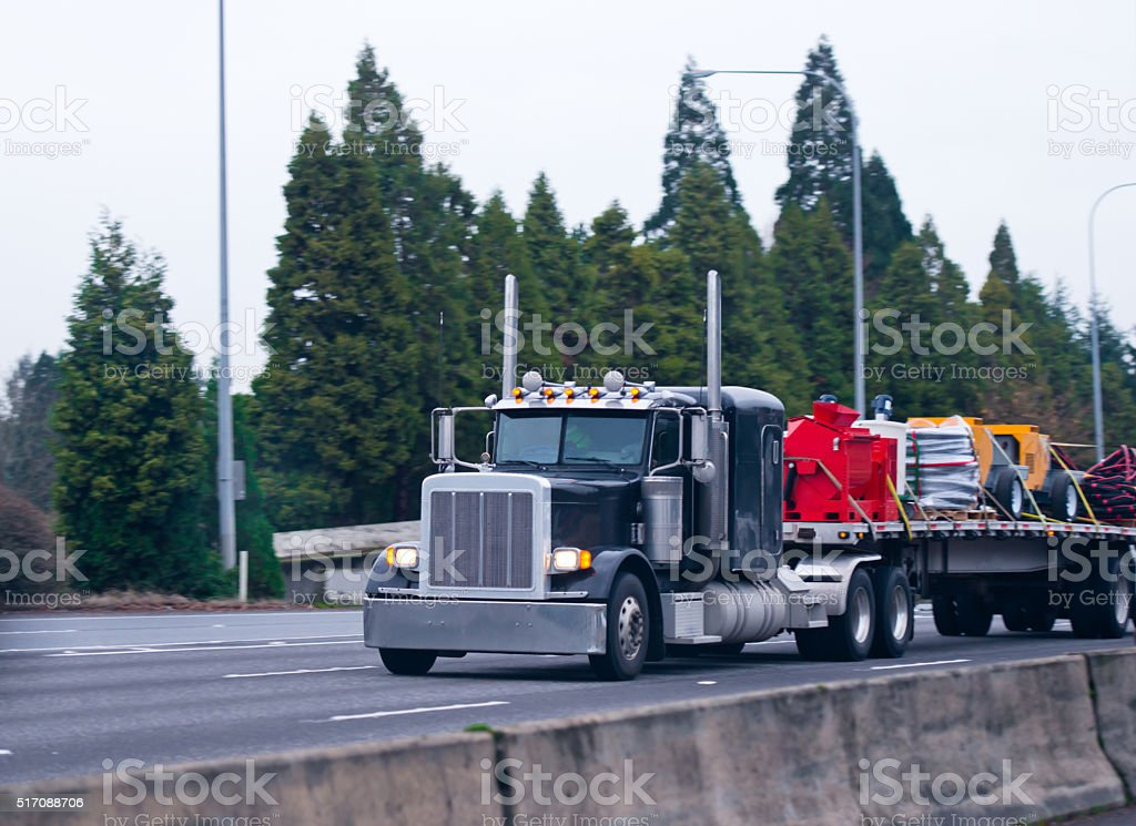 Classic black semi truck big rig flat bed commercial load stock photo