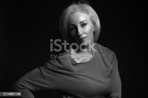 Classic black-and-white dramatic portrait of an elderly blonde woman in Studio on black background