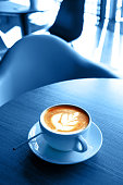 Classic blue cup of hot cappucino on the wooden table. Early morning breakfast