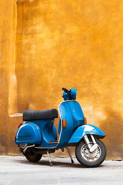 classic azul scooter contra amarillo grunge wall, toscana, italia - vintage vespa fotografías e imágenes de stock