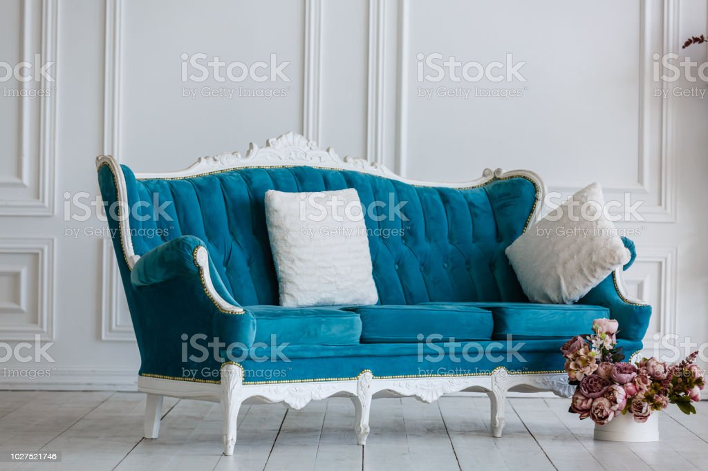 Classic blue sofa in a luxurious white room. artificial fireplace. on...