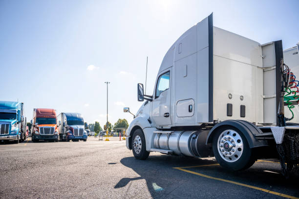 Classic bonnet big rig white semi truck tractor stand on the truck stop parking lot across another semi trucks standing in row for truck drivers rest stock photo