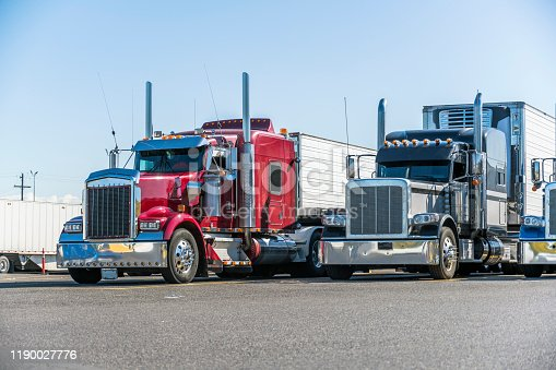 Different makes and models industrial grade professional big rigs semi trucks standing in row on the truck stop parking lot at evening time waiting to continued delivery schedule