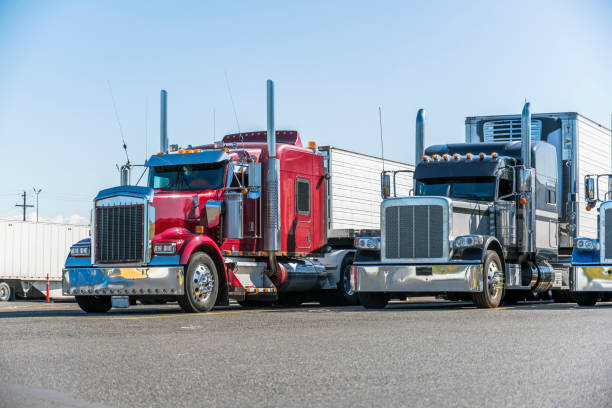 Classic bonnet big rigs semi trucks with reefer semi trailers standing in row on truck stop parking lot waiting for delivery schedule stock photo
