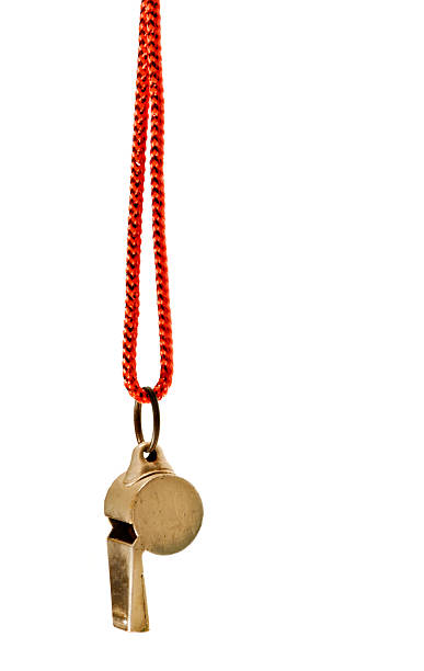 Classic brass whistle with red cord against white background stock photo