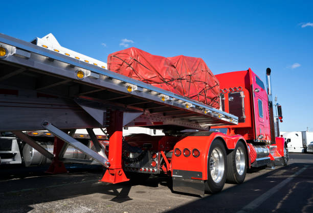 classic bright red american big rig semi truck with flat bed semi trailer standing on the truck stop with covered cargo - lorries unloading stock photos and pictures