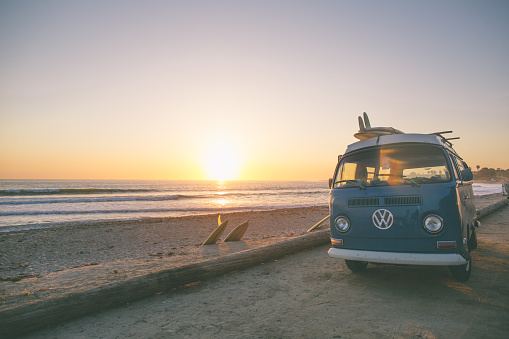 San Onofre, CA, USA - April 10, 2017:  A current but timeless image of a 60's VW Bus, parked at San Onofre Surf beach.  Single fin classic longboards liter the scenery as the surfers enjoy the waves in the fading light of the day.
