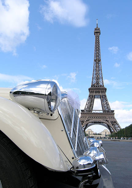 Classic Car and Eiffel Tower Classic car with bow on the Champ de Mars in front of the eiffel tower. skeable stock pictures, royalty-free photos & images