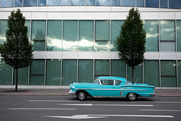 classic auto fahren an modernen bürogebäude - moderne 50er jahre mode stock-fotos und bilder