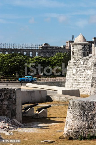 A classic 1950s car drives past an old fort in the city of Havana, Cuba.