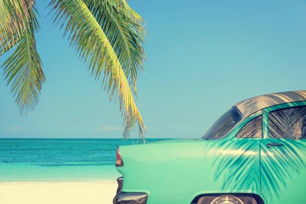 oldtimer an einem tropischen strand mit palme, vintage prozess - urlaub in kuba stock-fotos und bilder