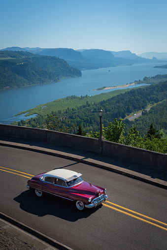 A classic American car on a scenic summer road