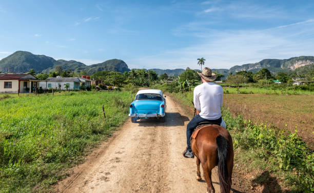 Classic car passes a man on horse in Vinales, Cuba stock photo