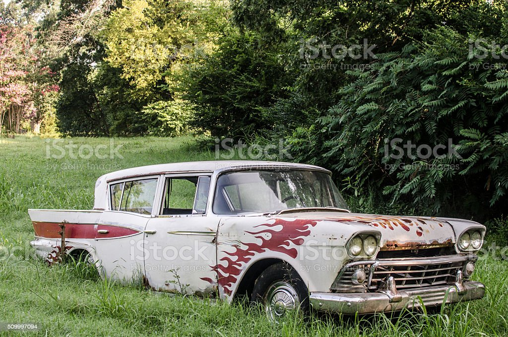 Classic car with flame paint job in overgrown field stock photo