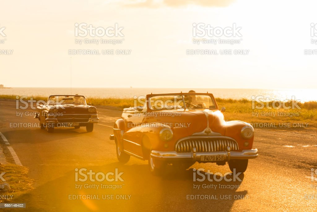 Classic cars driving along the coast in Cuba stock photo
