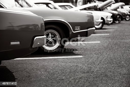 Photograph of classic cars parked in a row.