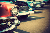 Photograph of classic cars with close-up on headlights parked in a row.