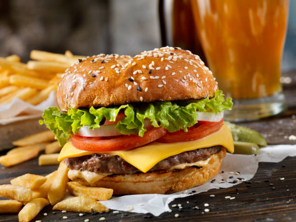 Classic Cheeseburger on a Brioche Bun with Fries and a Beer Classic Cheeseburger on a Brioche Bun with Fries and a Beer bacon cheeseburger stock pictures, royalty-free photos & images