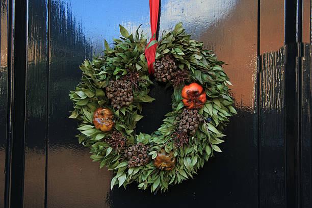 klassische weihnachtskranz mit dekorationen auf einem zimmer - türbänder stock-fotos und bilder