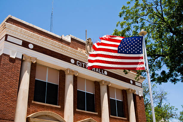 Classic City Hall The American flag flies in from of a classic city hall. local government building stock pictures, royalty-free photos & images