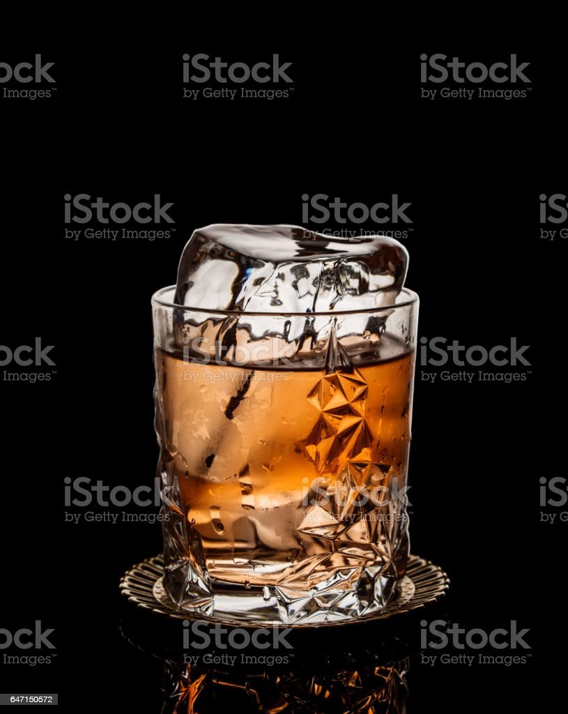 Classic cocktail with block of ice over black background стоковое фото
