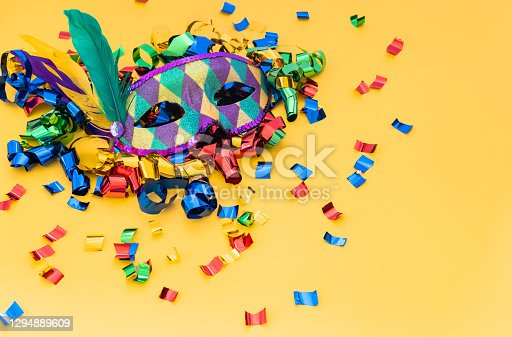 Classic colorful carnival mask with feathers and confetti on colored background. Concept of costume festivals, parades and carnivals.