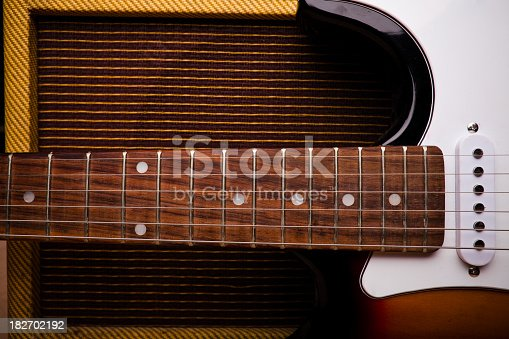 Still life of a mid-20th-century electric guitar leaning against a vintage amplifier