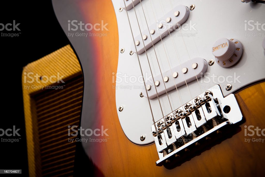 Still life of a mid-20th-century electric guitar leaning against a...