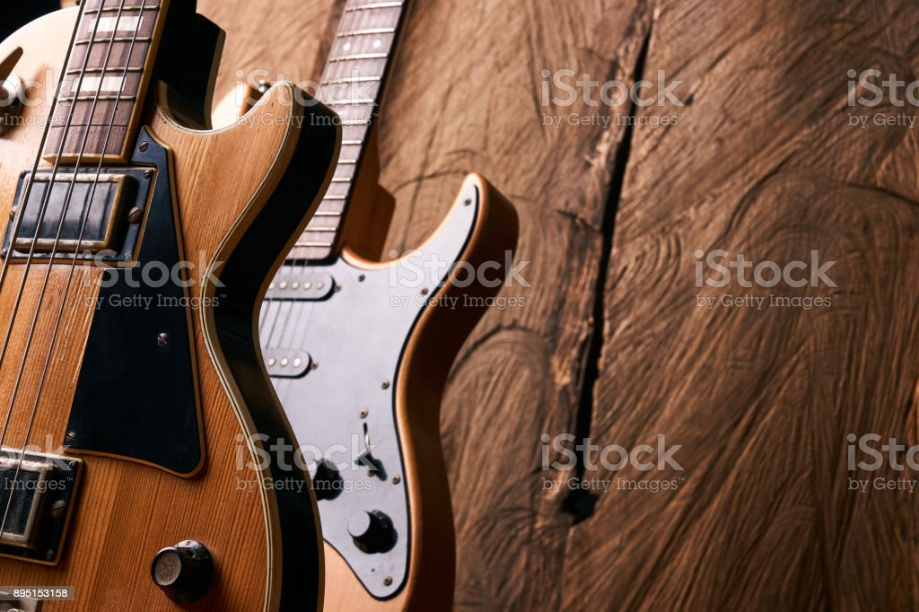 Classic electric guitar and wooden electric bass guitar on wooden...