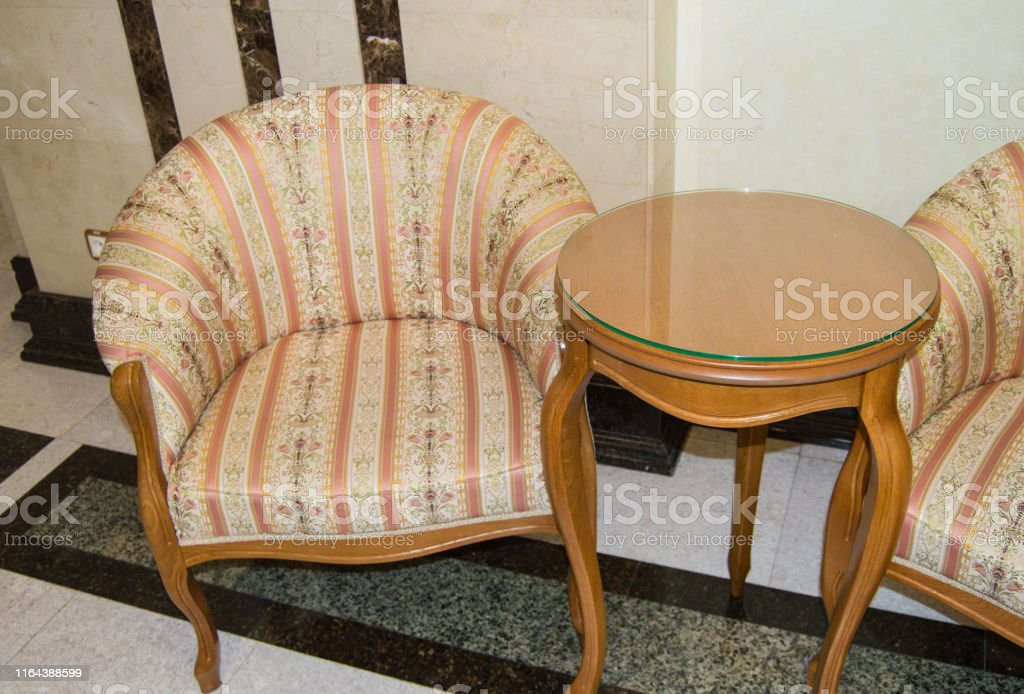 Classic Elegant Armchair And A Small Wooden Table With Curved Legs Made In Vintage Retro Style Marble Floor And Walls In The Living Room Of A Luxury Hotel Stock Photo Download