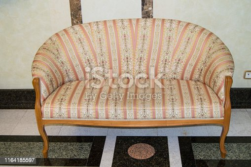 Classic elegant sofa with textile upholstery and wooden legs, made in vintage retro style, marble floor and walls in the living room of a luxury hotel.