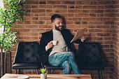 Classic elegant stylish smart clever handsome attractive bearded business shark, ceo in jacket and jeans, waiting for appointment, reading news-paper at workplace, workstation