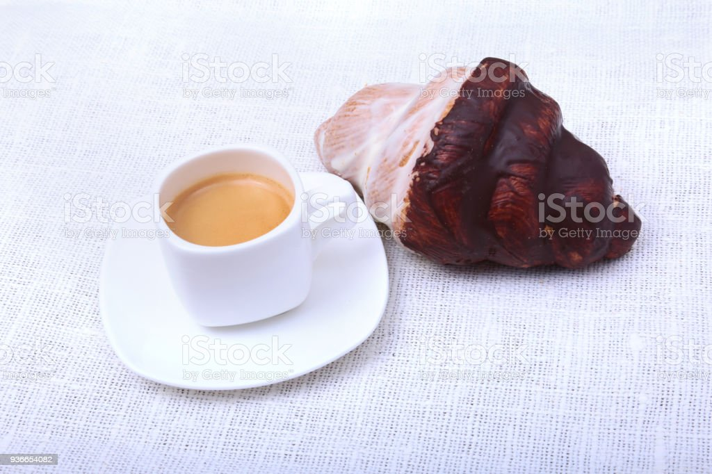 Classic espresso in white cup and croissant on white background. Top view. stock photo