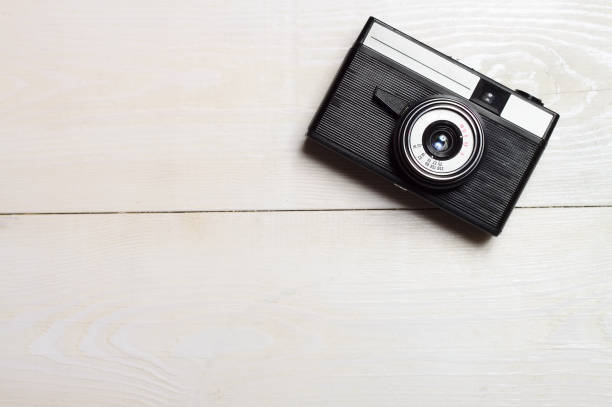 Classic film camera on white wooden background. stock photo