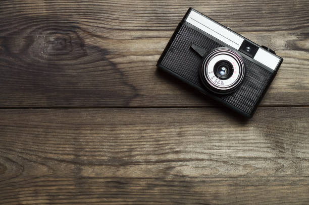 Cтоковое фото Classic film camera on wooden background.