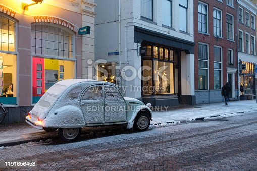 Classic French Citroën 2CV car on a snowy street during winter in the old town of Zwolle during a cold December afternoon.