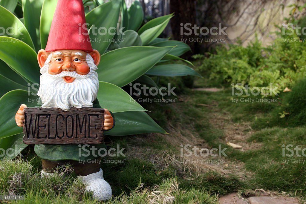 Classic garden gnome with welcome sign stock photo