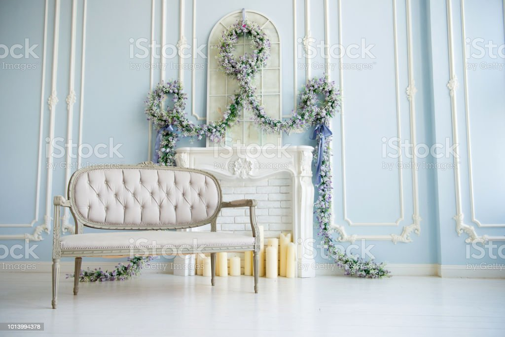 Classic gray sofa in a luxurious white room. artificial fireplace. on the fireplace. the room is decorated with flowers стоковое фото