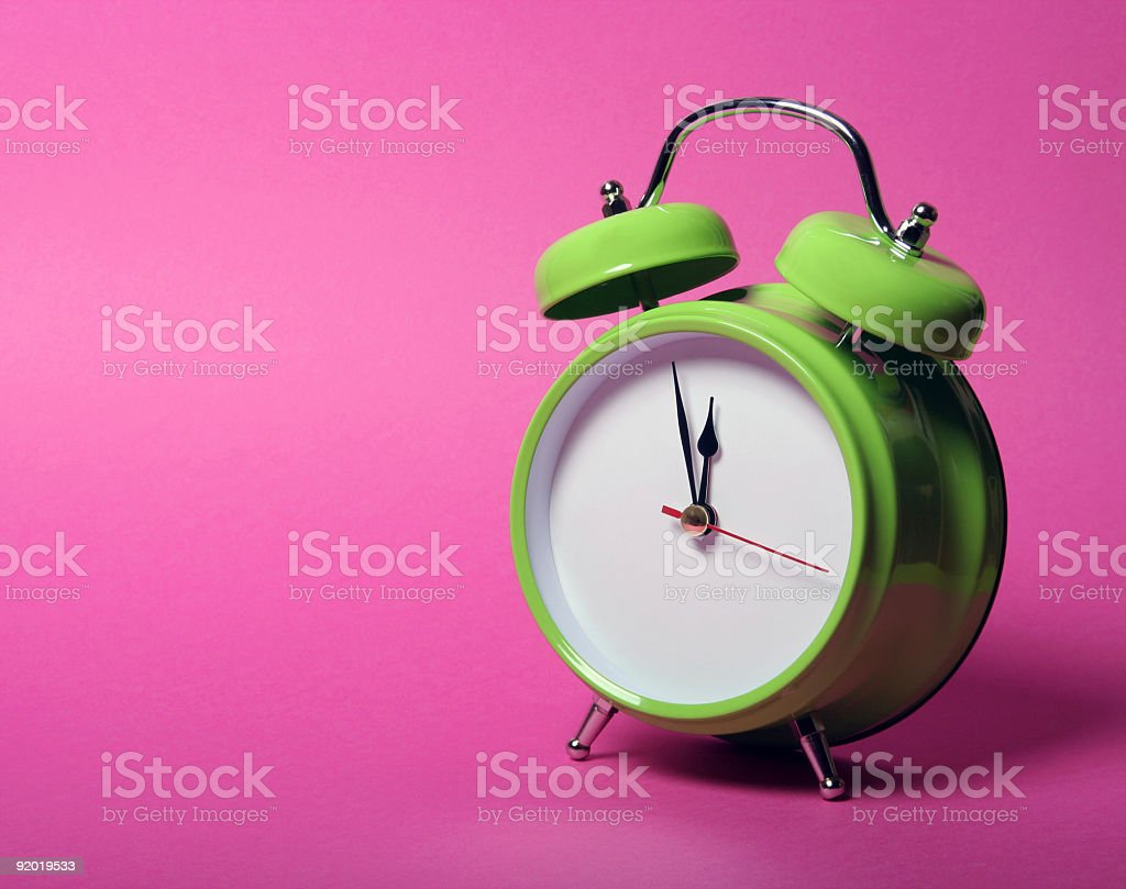 Classic green alarm clock on vibrant pink background royalty-free stock photo