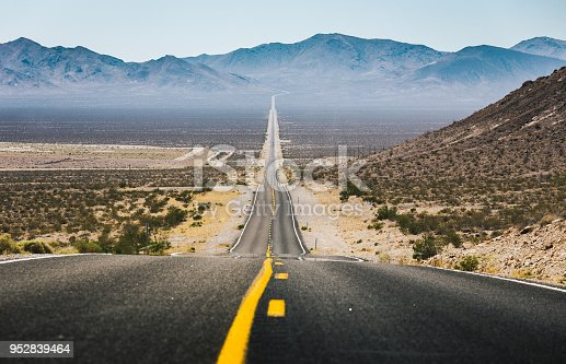 Classic low angle view of an endless straight road running through the barren scenery of the American Southwest with extreme heat haze on a beautiful sunny day with blue sky in summer
