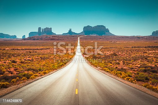 Classic panorama view of historic U.S. Route 163 running through famous Monument Valley on a beautiful sunny day in summer, Utah, USA