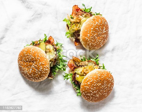 Classic homemade burger with pork cutlet, bacon, pickles, fried onions and mayonnaise mustard sauce on light background. Copy space