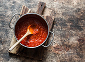 Classic homemade tomato sauce in the pan on a wooden chopping board on brown background, top view. Pasta, pizza tomato sauce. Vegetarian food