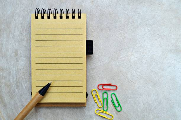 A classic horizontal photograph of a yellow beige plain page of a spiral bound vertical notepad along with a black and brown color pen and colourful paper clips placed  over a wooden look beige color grungy background. stock photo