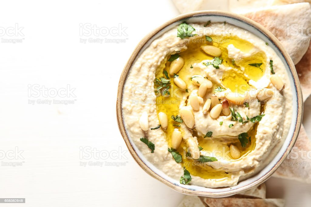 Classic hummus with herbs, olive oil in a vintage ceramic bowl a stock photo