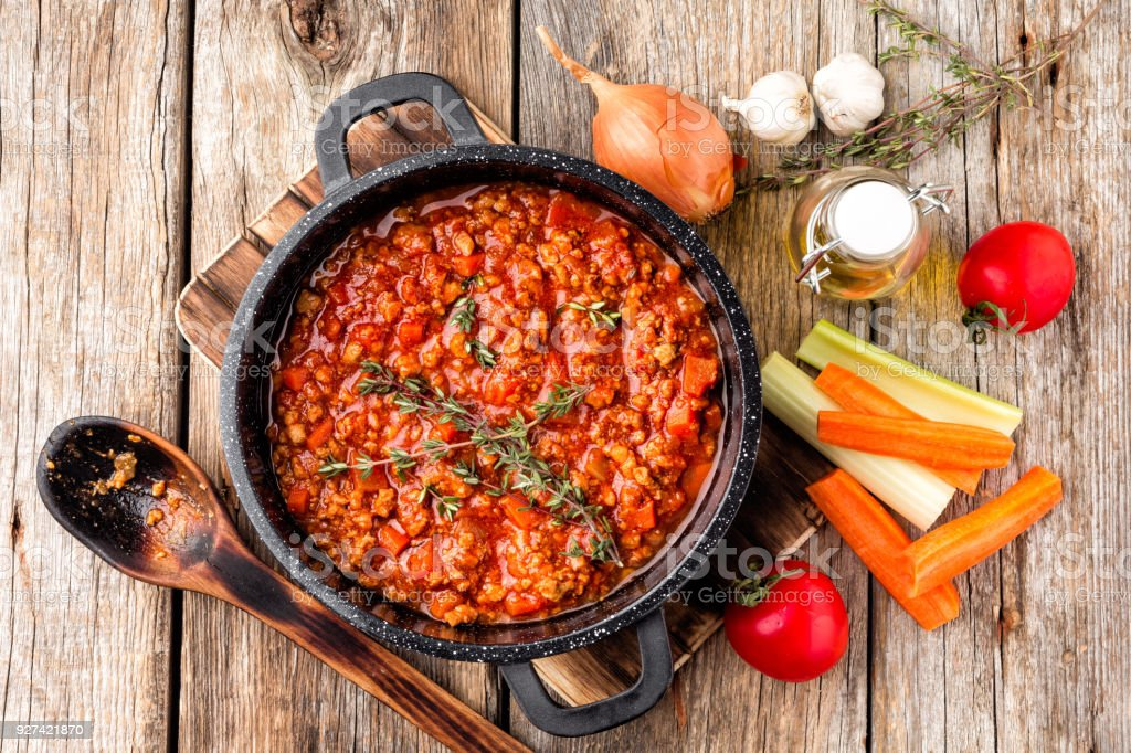 classic italian bolognese sauce stewed in cauldron with ingredients on wooden table, top view stock photo