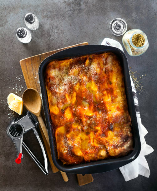 classic italian eggplant lasagna with vegetables and red wine in baking dish on a gray stone background .spilled parmesan, rosemary, old spoon . view from above. italian food. - auberginen parmesan lasagne stock-fotos und bilder